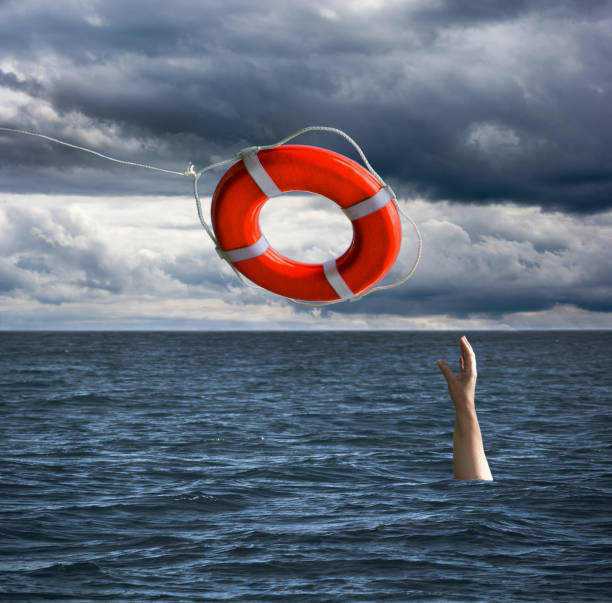 Life Saver Rescuing a Drowning Person in the Sea stock photo