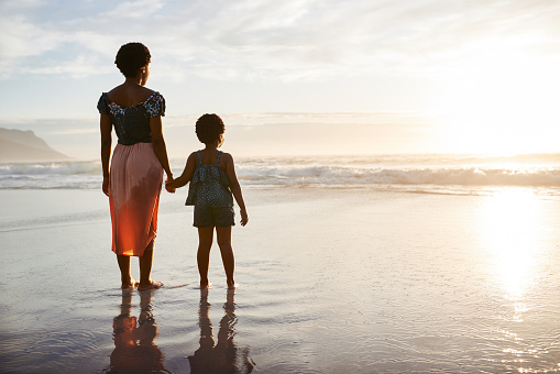 Shot of a young woman spending time at the beach with her adorable daughter