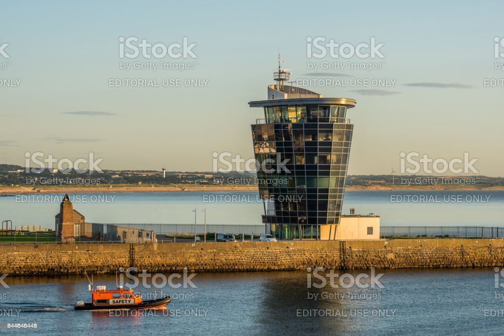 Lifeboat passes the Marine Operations Tower at Aberdeen Harbour. stock photo