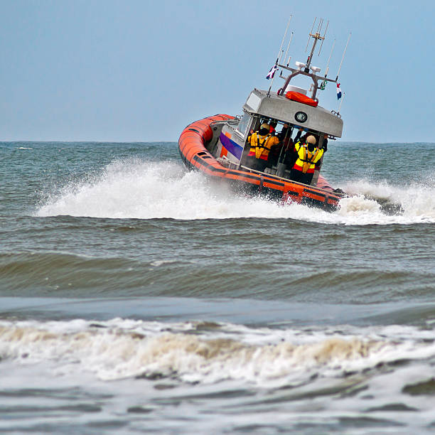 a lifeboat rides a wave as it sets off into action - livbåt bildbanksfoton och bilder