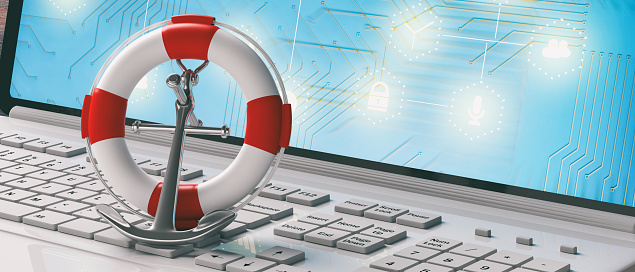 istock Lifebuoy and navy ship anchor on computer laptop keyboard, banner. 3d illustration 1075008916