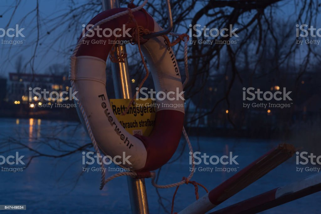 A lifebuoy at night by a German lake in Berlin in the middle of winter - Writing partially visible says 'Berlin Firefighters' and 'Misuse punishable' stock photo