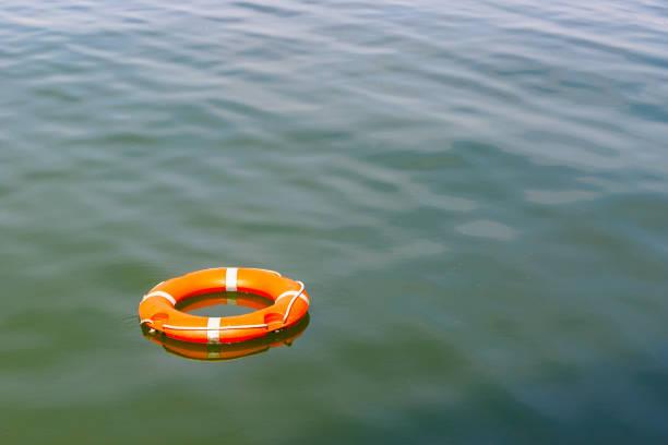 ein rettungsring auf dem wasser schwimmt - sos einzelwort stock-fotos und bilder