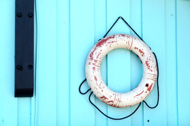 Lifebuoy  hanging on a blue wooden wall of a cabin in Tofino, British Columbia stock photo