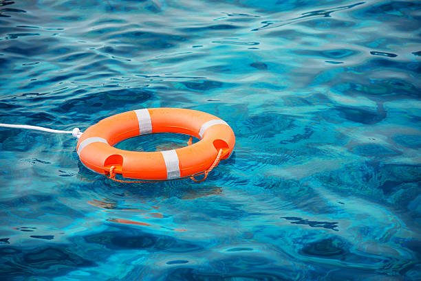 Lifebuoy in a stormy blue sea Lifebuoy in a stormy blue sea buoy stock pictures, royalty-free photos & images
