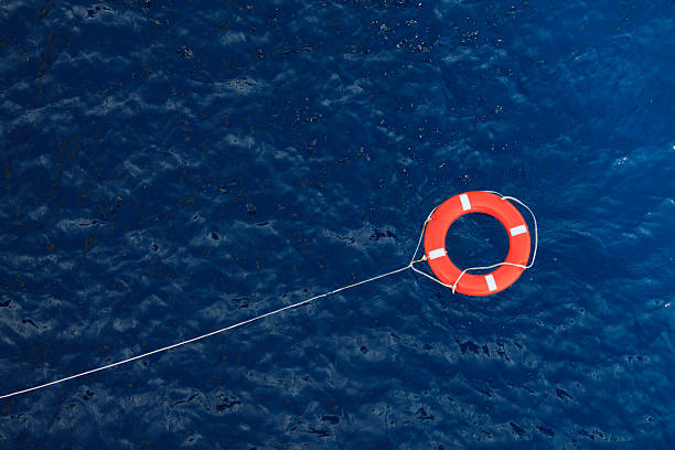 Lifebuoy in a stormy blue sea, safety equipment in boat Lifebuoy in a stormy blue sea, safety equipment in boat buoy stock pictures, royalty-free photos & images