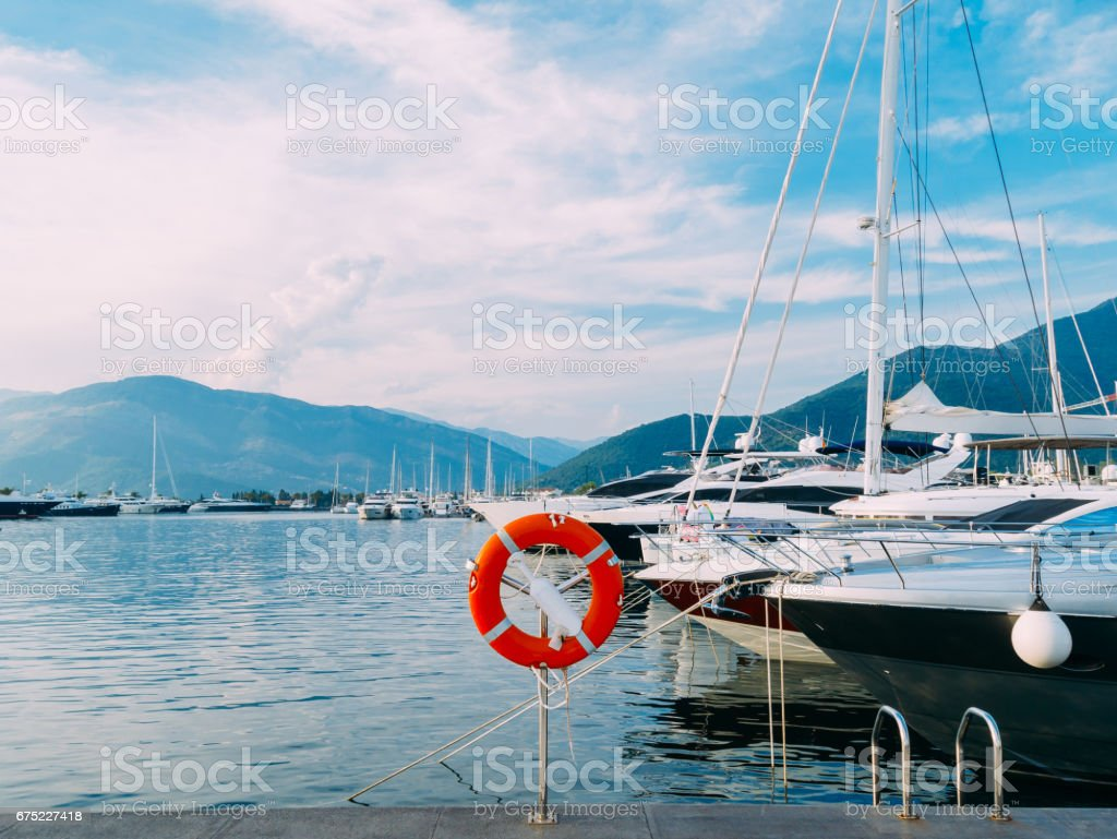 Lifebuoy in the marina for yachts. Red circle on the boat dock royalty-free stock photo