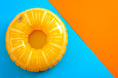 Summer vacation and safety equipment for swimming with a life buoy isolated on an orange and blue minimalist background with copy space