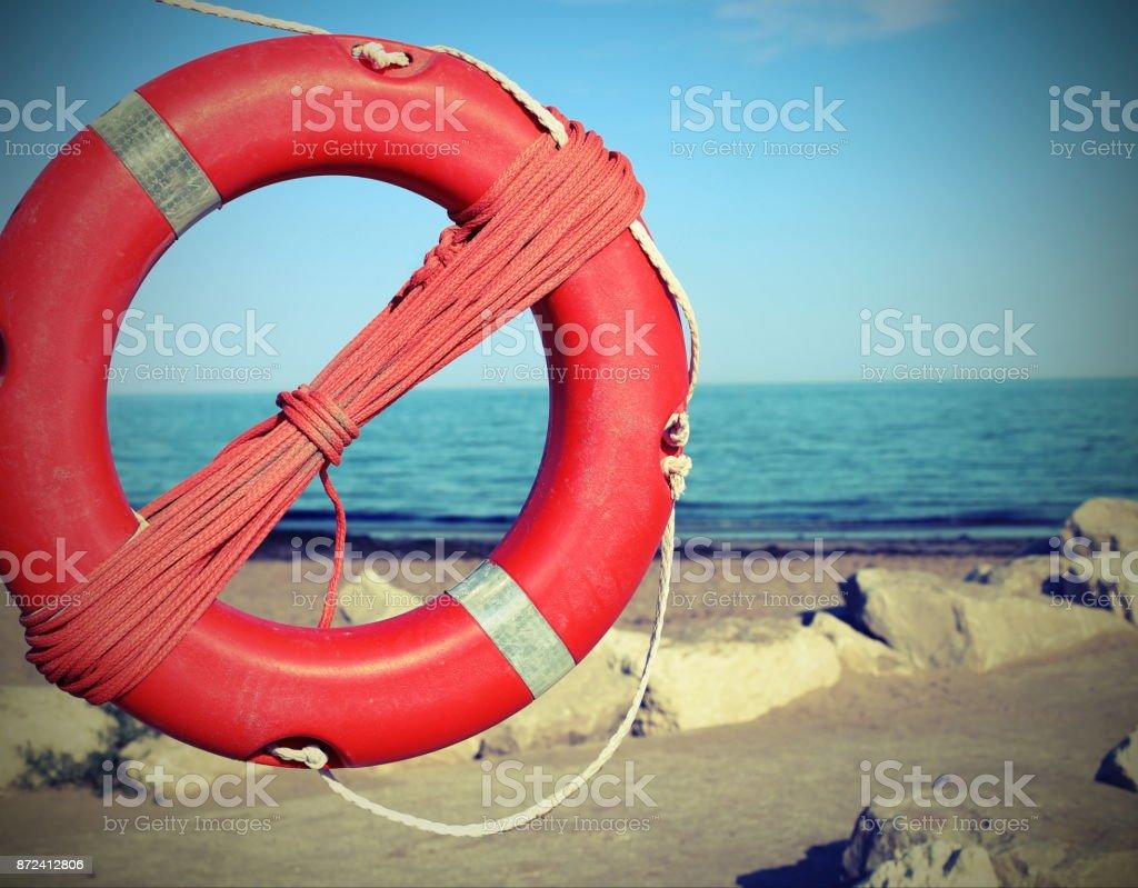 lifebuoy near rocks at the sea in summer stock photo