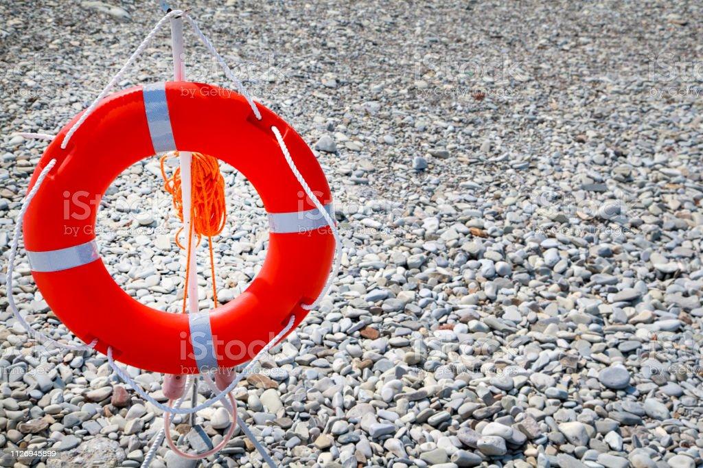 lifebuoy on a sea beach background, sea pebble, copy space stock photo