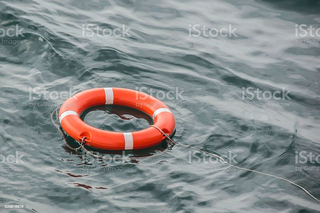 lifebuoy thrown to assist floats on water stock photo