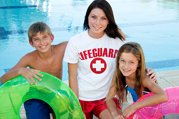 Lifeguard And Children Female lifeguard with two young child swimmers. lifeguard stock pictures, royalty-free photos & images