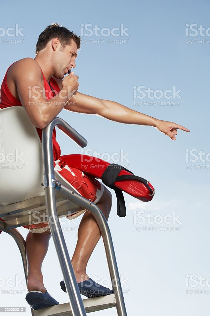 Lifeguard blowing whistle stock photo