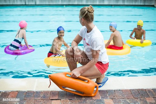 istock Lifeguard holding rescue can while children swimming in pool 845435586