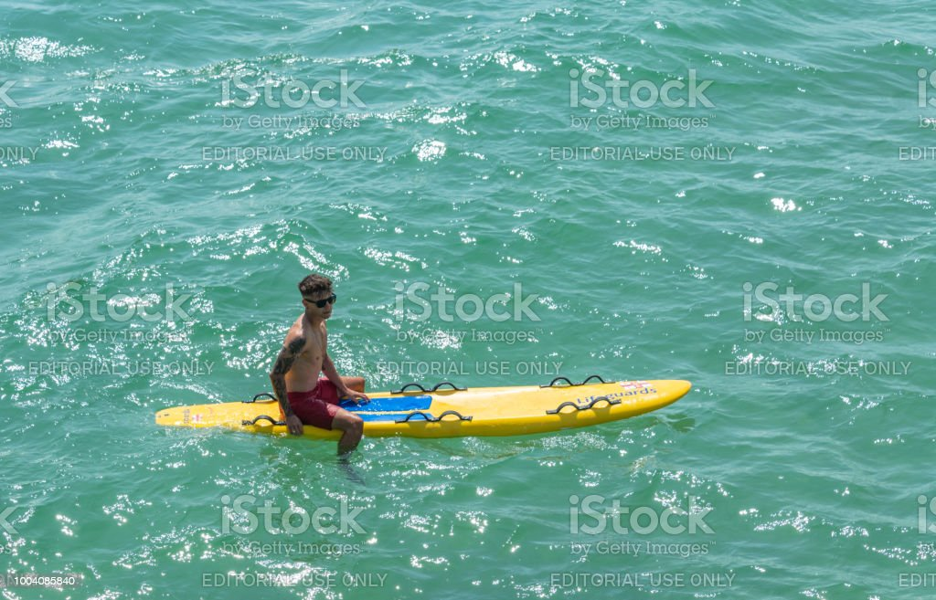 RNLI lifeguard on a surf board in Bournemouth, UK stock photo