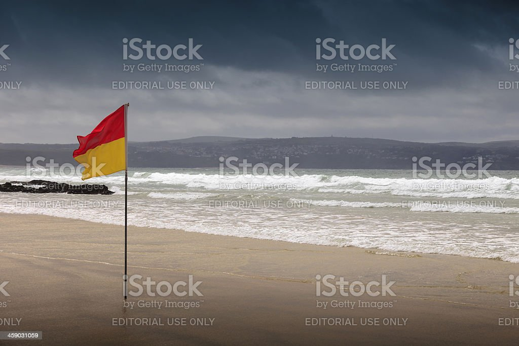 lifeguard on duty flag at Gwithian royalty-free stock photo