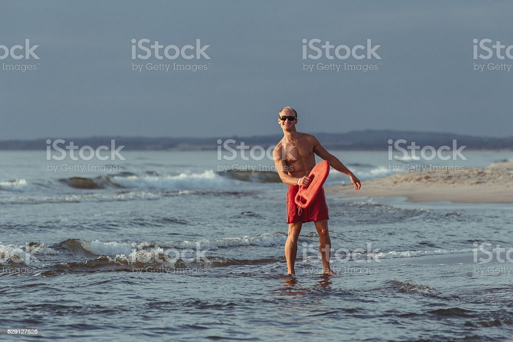 lifeguard on the beach with glasses, with a life buoy - foto de acervo