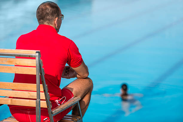 Lifeguard Lifeguard in chair, overlooking swimming pool lifeguard stock pictures, royalty-free photos & images