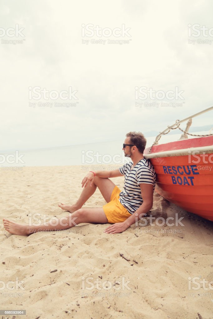 Lifeguard posing with his boat on the beach. royalty-free stock photo