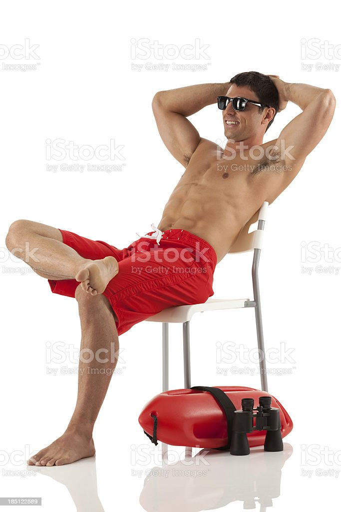 Lifeguard resting on a chair and smiling royalty-free stock photo