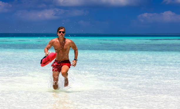 Lifeguard running in turquoise waters Male lifeguard running in turquoise waters in the Maldives lifeguard stock pictures, royalty-free photos & images