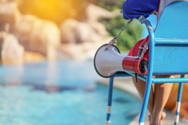 rettungsschwimmer auf stuhl sitzend mit megaphon am pool für die bewachung von leben - wasser sicherheitsausrüstung stock-fotos und bilder
