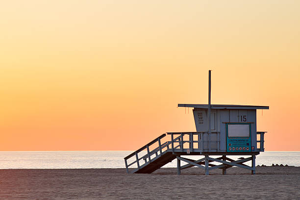 Lifeguard station at the empty beach during sunset stock photo