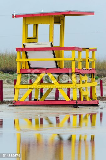 Lifeguard station in the off season, away from the beach, reflected in a puddle of rainwater in parking lot on Galveston Island, Texas, USA, on an overcast morning in winter