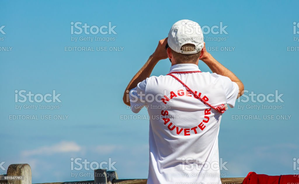 Lifeguard swimmer ('Nageur sauveteur' in French) watching people through binoculars stock photo