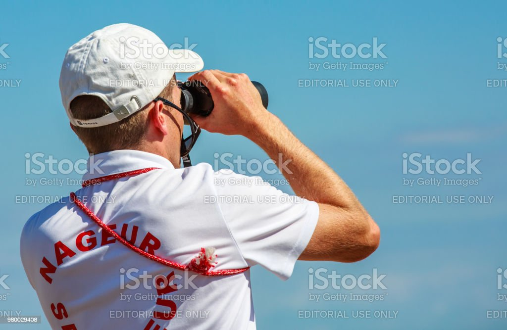 Lifeguard swimmer ('Nageur sauveteur' in French) watching people through binoculars stock photo