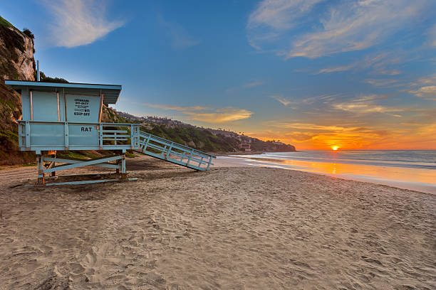 Lifeguard Tower at Sunset on Beach with Amazing Clouds stock photo