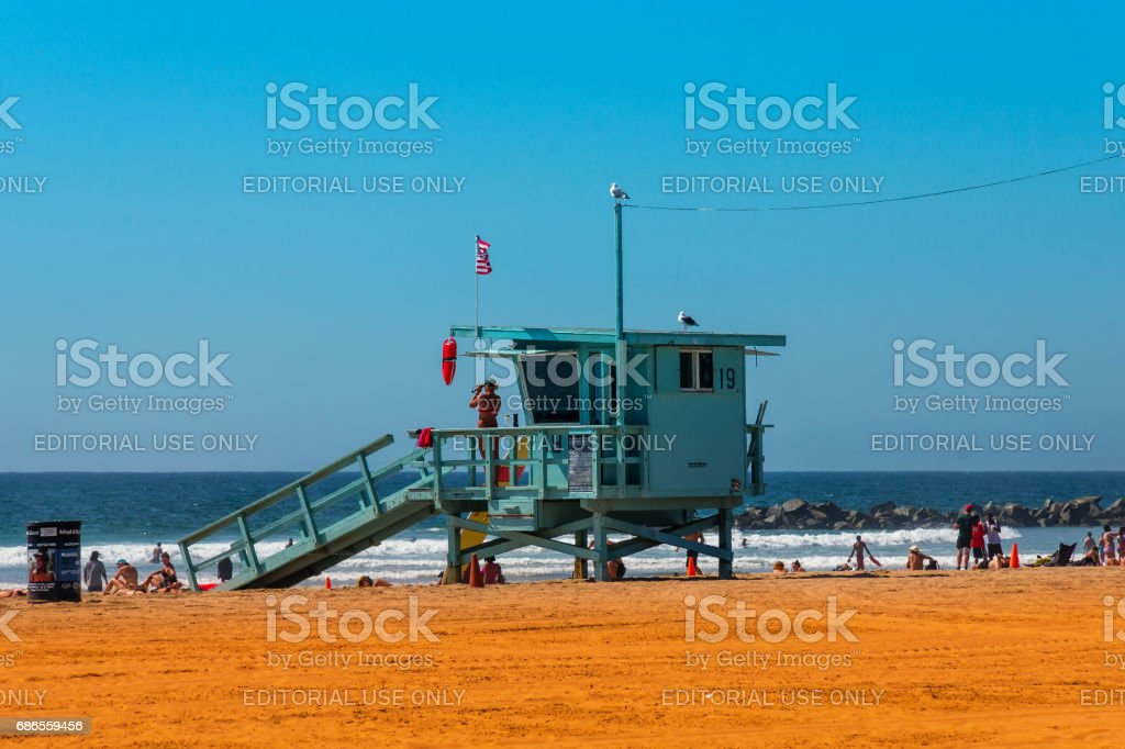 Santa Monica, Los Angeles, CA - September 24, 2015: Lifeguard Tower with woman lifeguard on duty at the beach of Santa Monica. Baywatch tower with colorful sky and beach. stock photo