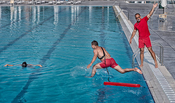 Lifeguard training course Lifeguard training course - rescuing victim from swimming pool lifeguard stock pictures, royalty-free photos & images