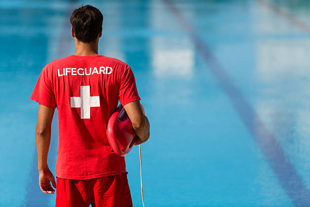 Lifeguard watching swimming pool Rear view of male lifeguard with emergency equipment in red uniform watching swimming pool. lifeguard stock pictures, royalty-free photos & images
