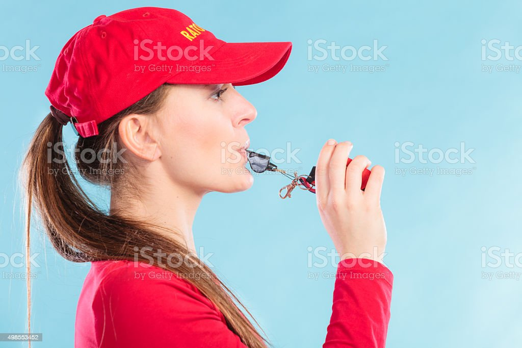 Lifeguard woman blowing whistle. stock photo