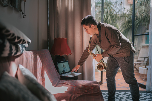 Lifehack asian chinese mid adult man practicing saxophone at living room online virtual class with his tutor using laptop