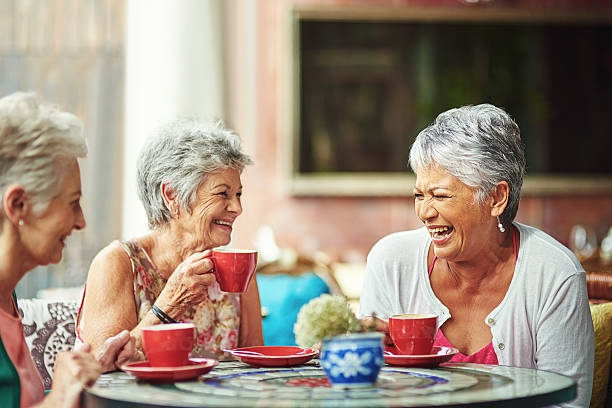 Lifelong friends catching up over coffee stock photo