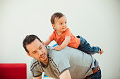 An adorable mixed-race boy is climbing on to his father's back as they play together indoors.