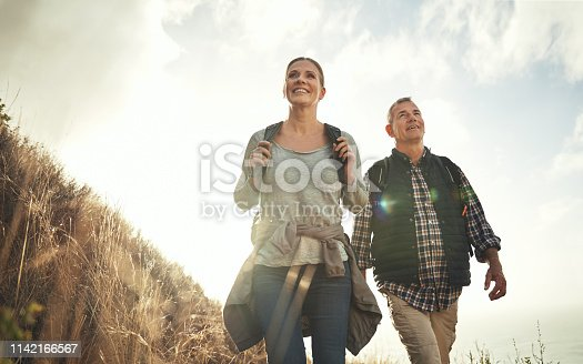 Shot of a mature couple hiking through the mountains