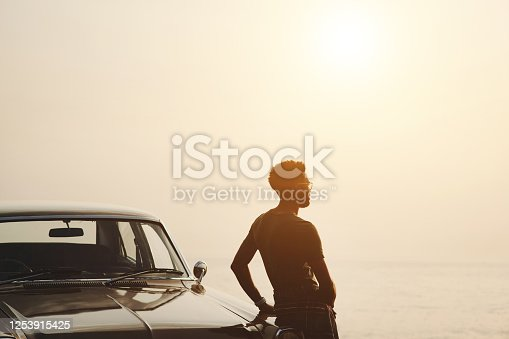 Rearview shot of a young man stopping to look at the view during a road trip