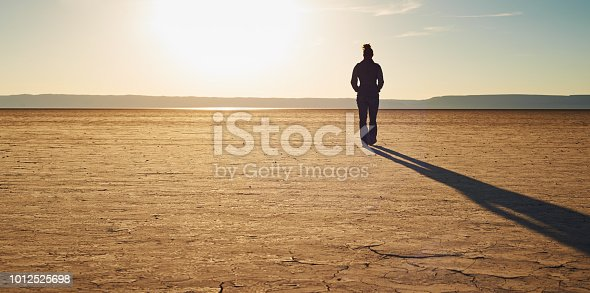 Shot of a young woman walking alone in the desert