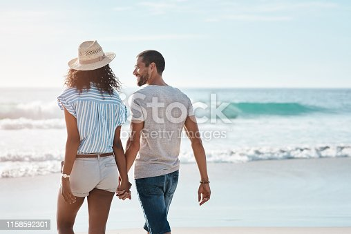 Rearview shot of a young couple walking along the beach