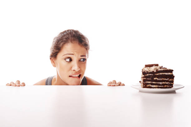 Life's too short to say no to cake Studio shot of an attractive young woman being tempted by something sweet temptation stock pictures, royalty-free photos & images