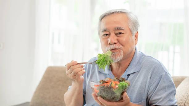 Lifestyle Asian senior man ,old man feel happy enjoy eating diet food fresh salad on sofa stock photo