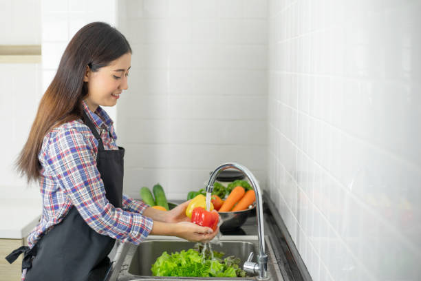 Lifestyle beautiful Asian healthy girl fill Happy , Washing vegetables in the kitchen sink stock photo