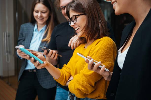 Lifestyle-Geschäftsleute haben gemeinsam Spaß und nutzen modernes Smartphone im Büro. Digitale Gadgets mit Konzept. – Foto