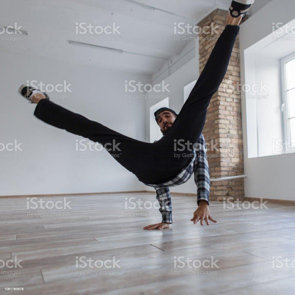 Lifestyle dancing. Handsome young man dancing break dance indoors