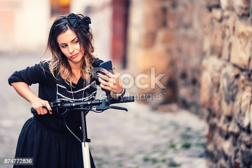 874772840istockphoto Lifestyle details - portrait of woman taking selfie with smartphone, relaxing on electric scooter 874772836