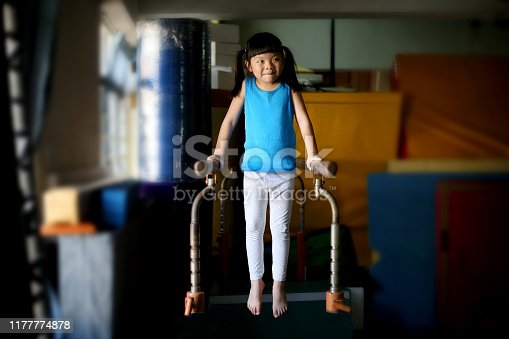 A young preschool girl is enjoying fitness training on gymnastic parallel bar.