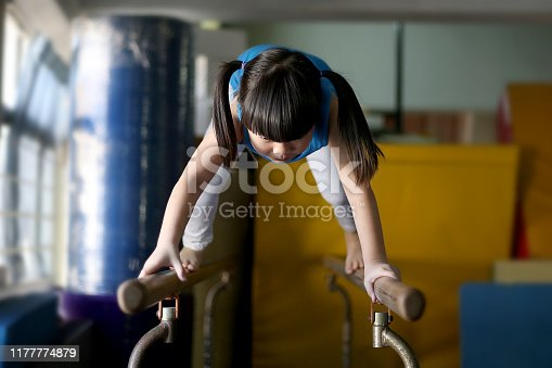 A young preschool girl is enjoying fitness training on gymnastic parallel bar.